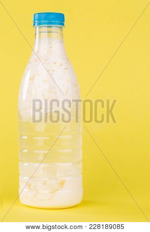 Sour Milk In A Plastic Bottle. Located On The Yellow Background.