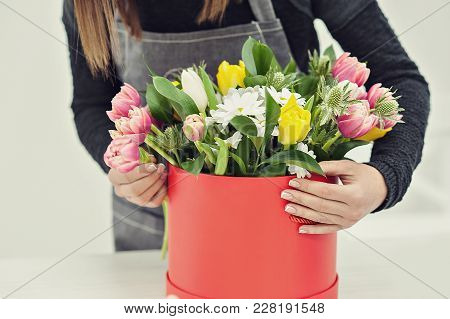 Close-up Hands Of Florist With Flowers. Florist Holding Blooming Bouquet Of Pink Tulips On A Linen B