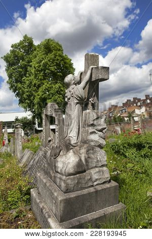 London, England - July 12, 2017 Gravestones In Tower Hamlets Cemetery Park London. Girl Clinging To