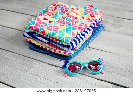 Kidswear Pile And Sunglasses On A White Wooden Background. Stack Of Colorful Cotton Children Clothin