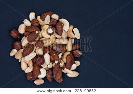 Varied And Colorful Nuts. View From Above. Flat Lie. Black-and-blue Background.