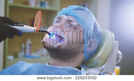 Doctor And Patient With Retractor In The Dental Office, Cleaning With Ultraviolet Light And Orange P