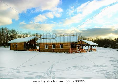 Three Bright Yellow Houses For Rest In The Middle Of A Snowy Meadow In The Forest During The Daytime