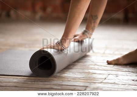 Hands Of Young Yogi Woman Folding Black Yoga Or Fitness Mat After Working Out At Home In Living Room