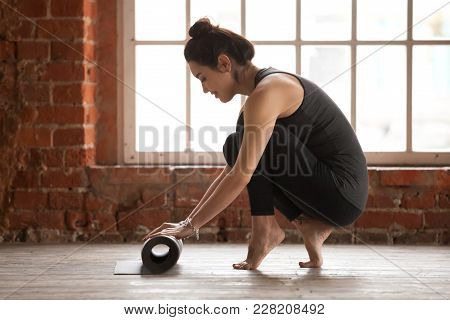 Attractive Happy Fit Young Woman Rolling Up Black Yoga Or Fitness Mat After Working Out In Loft Yoga