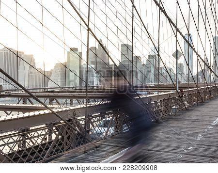Blured Cyclist Cycling Across Brooklyn Bridge. New York City Manhattan Downtown Skyline In Sunset Wi