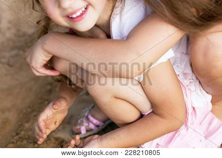 Two Happy Little Girls Laughing And Embracing At The  Summer Park