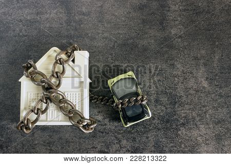 Small White House, Car And A Decorative Chain On A Dark Background. Concept  -  Risks, Lose Property