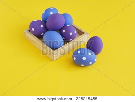 Easter Eggs In A Tray For Eggs. Eggs On A Stand. Yellow Background. The Colors Are Purple, Yellow An