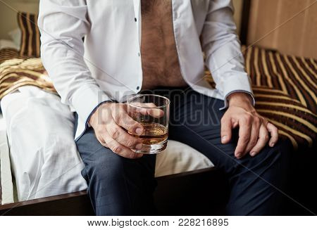 Overweight Businessman In Shirt Sitting On Couch And Holding Glass Of Whiskey, Brandy Or Cognac. Dru