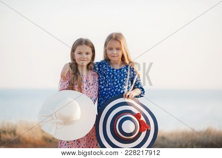 Two sisters, beautiful girls with long, straight, fair hair, wearing on their heads big straw hats a