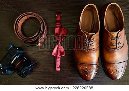 Close Up Of Brown Leather Male Shoes, Bow Tie, Belt And Camera On Wooden Background. Modern Man Or G