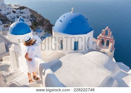 Redhead Woman Contemplating Next To The Traditional Church In Village Oia At Sunny Day. Lifestyle An
