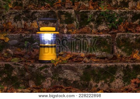 Luminous Hand Lantern Standing On A Dilapidated Stone Stairs Covered With Grass And Dry Leaves At Ni