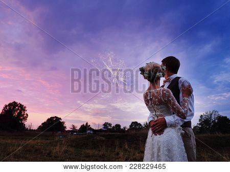 The Bride And Groom Stand By The Lake, After The Wedding Ceremony. Newlyweds Are Smiling, They Are H