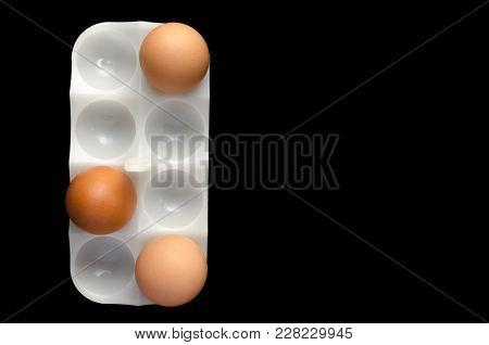 Three Chicken Eggs White Stand On Black Background,close Up.