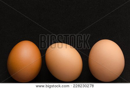 Three Brown Chicken Eggs Black Background, Close Up.