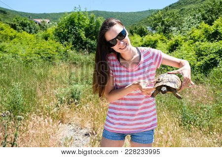 Close-up Woman Brunette In Sunglasses And Striped T-shirt And Jeans Shirt Keeping Turtle In Her Hand