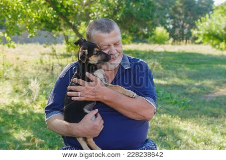Outdoor Portrait Of Senior Man With Black Little Puppy On The Hands