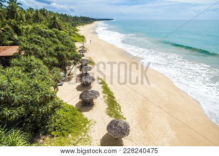 Tropical Long Beach With Beds And Umbrellas In Sri Lanka. Resort Beach In The Sunlight. Beauriful De