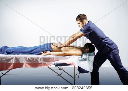 Strong Young Man Masseur Conducts Restoring Procedure And Drives Hands Along Spine And Along Back To