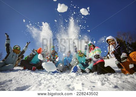 A group of friends of skiers and snowboarders fun throwing snow on top of the mountain. Ski resort Sheregesh. Russia.