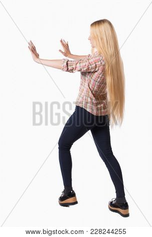 back view of woman pushes wall.  Isolated over white background. Rear view people collection. backside view of person. Girl with very long hair that shoves his hands in his side.