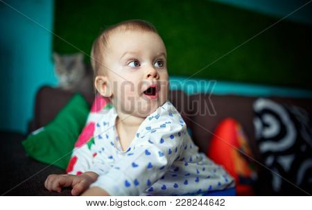 Lifestyle Portrait Of Surprised One Year-old Baby Girl In Her Room. Cat Background