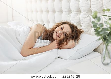 Portrait Of Beautiful Young Woman Being Satisfied After Pleasant Dreams And Good Sleep, Lies On Whit