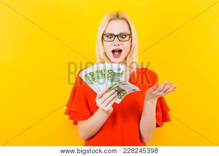 Portrait Of Surprised Woman In Glasses And Red Dress Isolated On Yellow Background Hold Fan Of Euro