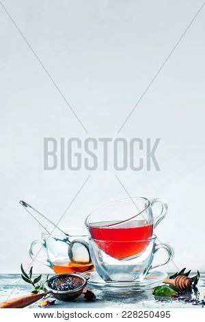 Stack Of Glass Cups Of Tea On A White Background With A Honey Spoon, Tea Strainer, Fresh Green Leave