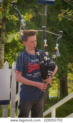 Portree, Scotland - 29 July, 2016 : A Yound Scotish Boy Playing Traditional Bagpipe At Portree, Scot