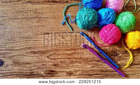 Colorful Yarn Balls And Hooks For Knitting And Crochet On Wooden Background