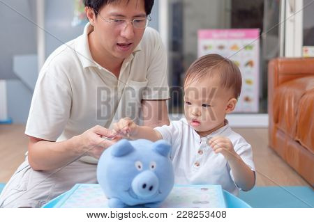 Father And Cute Little Asian 18 Months / 1 Year Old Toddler Baby Boy Child Putting Thai Coin Into Bl