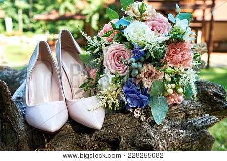 Close Up Of Beautiful Wedding Bouquet Of Pink And White Roses And Beige Shiny Bride Shoes On Wooden