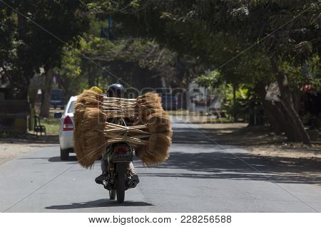 Labuanbajo, Indonesia - August 13, 2015: An Unidentified Man Is Carring A Big Amount Of Brooms On A