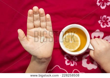 A Sick Boy Holding A Medicament In His Hand And Cup With A Hot L