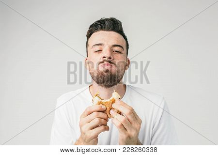 Close Up Of A Man Eating The Burger. He Is Enjoying The Process Of Tasting It. He Hasn't Been Eating