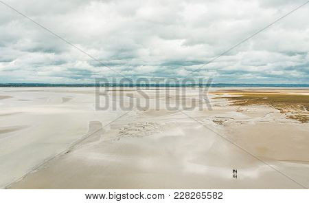 Unidentified People Walking On Sands During Low Tide Outside Le Mont Saint-michel Tidal Island In No