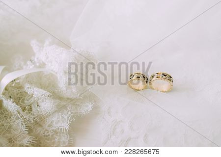 Two Wedding Gold Rings On Beautiful White Tulle With Lace Garter Close. Horizontal