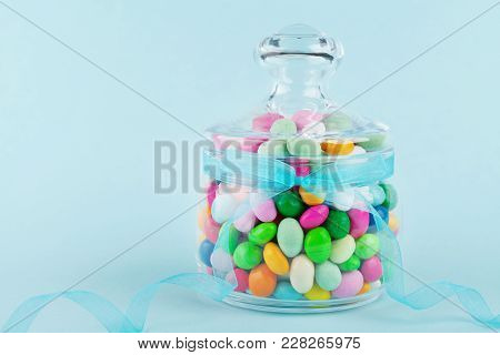 Glass Jar Stuffed With Colorful Candy Against Blue Background. Gifts For Birthday Or Happy Easter.