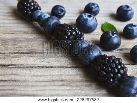 Fresh Ripe Blueberries And Blackberries On Rustic Wooden Table.bilberry Border.flat Lay,top View,sel