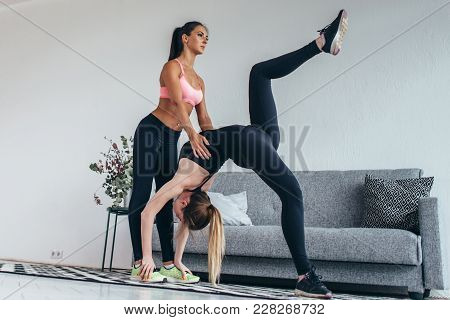 Fitness Woman Doing Advanced Bridge Pose Called One-legged Wheel With Assistance Of Instructor At Ho