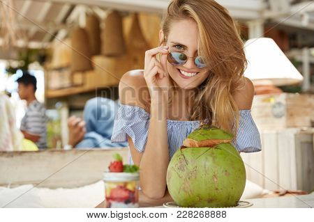 Pleasant Looking Young Female Wears Sunglasses, Blouse, Drinks Coconut Cocktail, Sits Against Cafe I