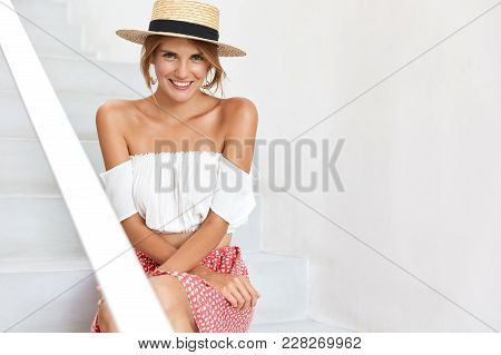 Horizontal Shot Of Attractive Woman In Fashionable Clothes, Sits On Stairs, Spends Summer Vacations