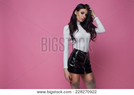 Beautiful Busty Woman In A Sexy Shorts With Long Brunette Hair Posing Against A Pink Studio Backgrou