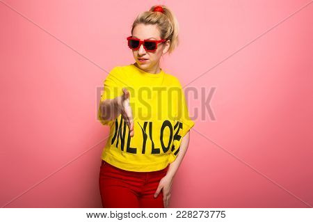 Attractive Woman In Yellow T-shirt, Red Jeans And Sunglasses Giving Her Hand For Handshake Isolated