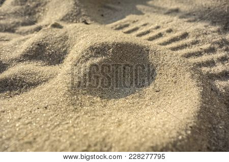 Background Of Large Raw Sand Decorated In The Form Of Dunes  In The Rays Of The Sunlight.