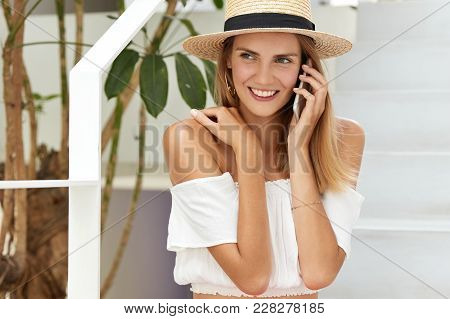 Indoor Shot Of Happy Female In Straw Hat, Sits On Stairs With Mobile Phone, Has Pleasant Conversatio