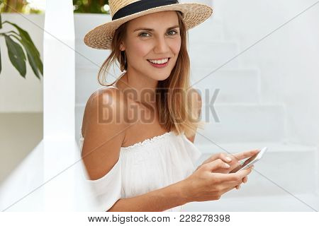 Positive Good Looking Female With Charming Smile, Wears Straw Summer Hat Shares Travel Post In Socia